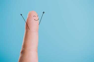 cropped view of one finger with happy face isolated on blue