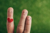 cropped view of fingers as happy couple and person with broken heart on green