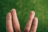oříznutý pohled lidských prstů jako pozitivní páry na zelené