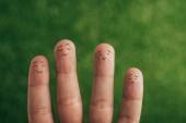 vista parziale delle dita umane felice su verde