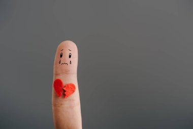 cropped view of one upset finger with broken heart isolated on grey