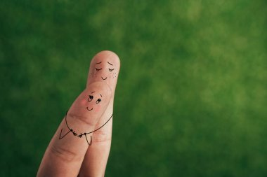 cropped view of smiling couple of fingers embracing on green