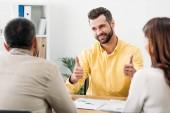 Selektivní fokus poradce u stolu a stopovat ups poblíž muž a žena v úřadu
