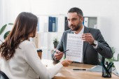 Photo selective focus of advisor sitting at table and pointing at contract with pen to woman in office