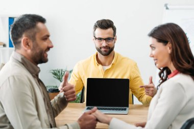 selective focus of advisor pointing with finger at laptop with blank screen on screen while investor holding woman hand and thumbing up in office