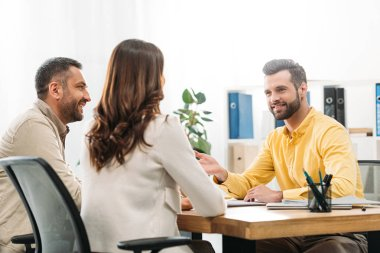 advisor sitting at table and smiling to man and woman in office