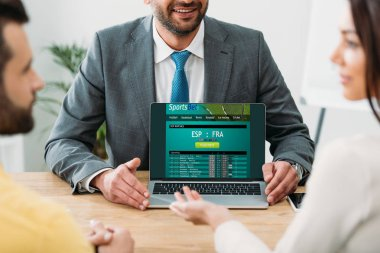 Selective focus of advisor pointing with fingers at laptop with sportsbet online website on screen to couple in office stock vector