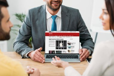 Cropped view of advisor sitting at table and laptop with bbc news website on screen with investors in office stock vector