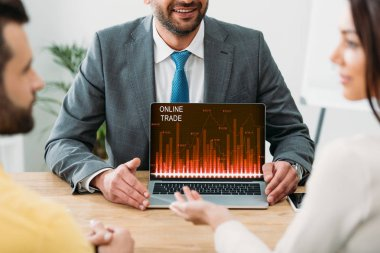 Cropped view of advisor sitting at table and laptop with online trade website on screen with investors in office stock vector