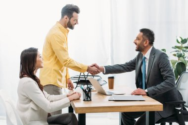 advisor and investor shaking hands over table wile woman sitting in office