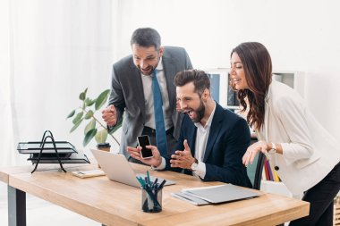 Colleagues at table looking to laptop and rejoicing in office stock vector