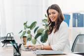 Üzletasszony ül asztal, laptop, gépelés, és mosolyogva hivatalban