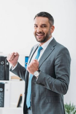 handsome businessman in grey suit showing yes gesture in office