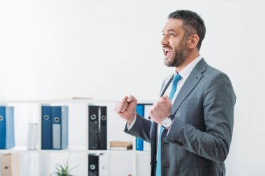 businessman standing and showing yes gesture in office