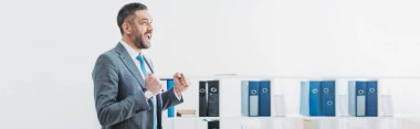 handsome businessman standing and showing yes gesture in office