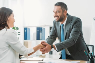 handsome advisor in suit shaking hands with investor at workplace
