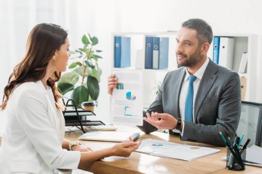 handsome advisor discussing document with investor at office