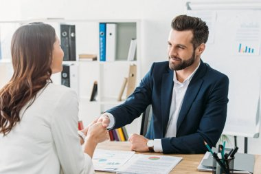handsome advisor in suit shaking hands with investor at workspace