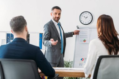 Selective focus of handsome advisor showing document to investors in suits at workplace stock vector