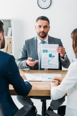 Selective focus of handsome advisor in suit showing document to investors at workspace stock vector