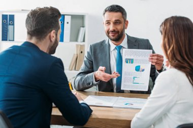 Selective focus of handsome advisor showing document to investors at workplace stock vector