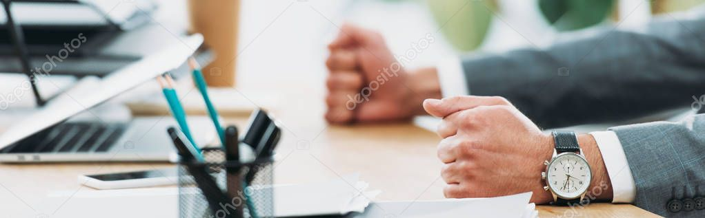 Cropped view of businessman at table with laptop and smartphone in office stock vector