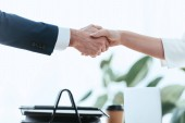 Photo selective focus of woman and man shaking hands at office