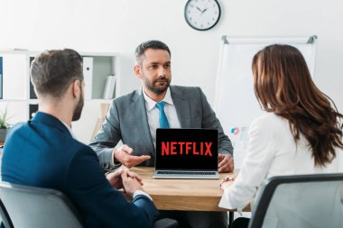 selective focus of advisor pointing with fingers at laptop with netflix website on screen at workplace