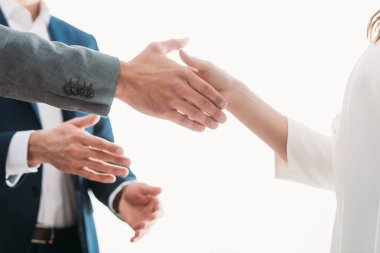 selective focus of men and woman shaking hands at office