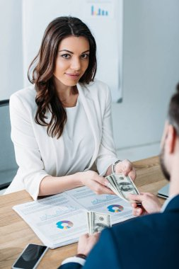 selective focus of attractive advisor taking money from investor at office