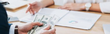 selective focus of man holding dollar banknotes at office
