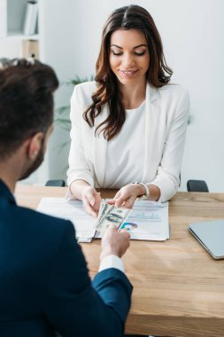 selective focus of beautiful advisor taking money from investor at office
