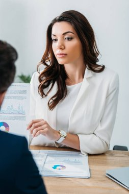 Selective focus of beautiful advisor showing document to investor in suit at workspace stock vector