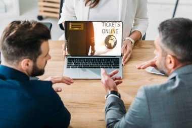 Selective focus of advisor showing to investors laptop with tickets online website on screen stock vector