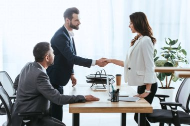 beautiful advisor and investor in suits shaking hands at office