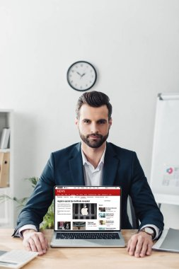 Handsome advisor in suit showing laptop with bbc news website on screen stock vector