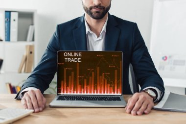 Cropped view of advisor in suit showing laptop with online tarde website on screen stock vector