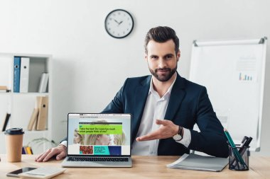 Handsome advisor in suit pointing with fingers at laptop with bbc website on screen at office stock vector