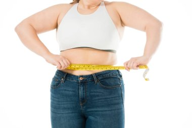 cropped view of overweight woman measuring waist isolated on white