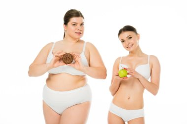 young slim woman holding green apple while overweight woman holding sweet doughnut isolated on white