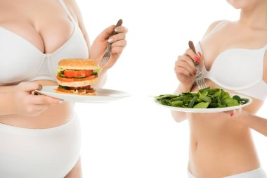 cropped view of slim woman standing with plate of green spinach leaves while overweight woman holding plate with burger isolated on white