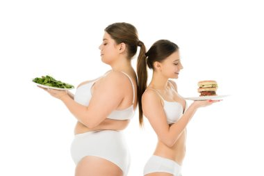 happy slim woman with burger standing back to back with upset overweight woman with green spinach leaves isolated on white