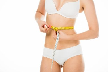 cropped view of slim woman in underwear measuring waist with centimeter isolated on white