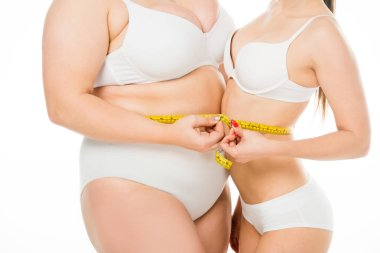 cropped view of body positive overweight woman and slim woman holding measuring tape together isolated on white