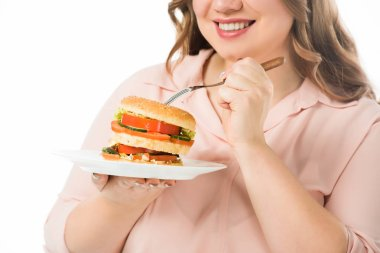 Cropped view of smiling woman eating tasty burger from plate with fork isolated on white stock vector