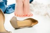 Selektivní fokus ženy stojící na špičkách s boty na podpatku na popředí