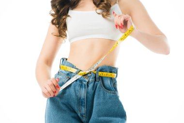 cropped view of woman holding measuring tape on big jeans isolated on white, lose weight concept