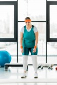 Photo upset overweight woman standing in sportswear in gym