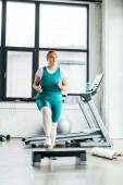 Molett nő lépés platform közeli edzőteremben fitness szőnyeg gyakorlása