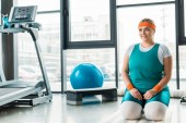 happy plus size woman sitting on fitness mat near  sport equipment